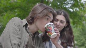 Unga lyckliga par i tillf?llig kl?der som spenderar tid i, parkerar tillsammans och att ha datumet Studenterna som dricker kaffe, arkivfilmer