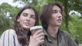 Unga lyckliga par i tillf?llig kl?der som spenderar tid i, parkerar tillsammans och att ha ett datum Flickan som dricker kaffe arkivfilmer