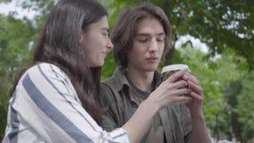 Unga lyckliga par i tillf?llig kl?der som spenderar tid i, parkerar tillsammans och att ha ett datum Studenterna som dricker kaff arkivfilmer