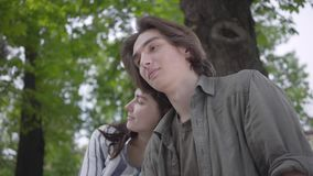 Unga lyckliga par i tillf?llig kl?der som spenderar tid i, parkerar tillsammans och att ha ett datum V?nner som sitter p? b?nken arkivfilmer