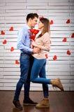 Unga lyckliga par med hjärta i handonbackground arkivbild