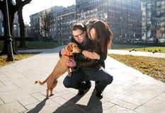Unga lyckliga par med hunden tycker om i en härlig dag Royaltyfri Bild