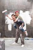 Unga lyckliga par med målarfärgrullen som har gyckel Arkivfoton