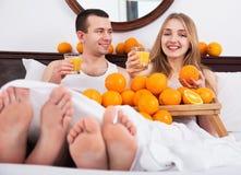 Unga lyckliga par med mogna apelsiner och nytt fruktsaft Fotografering för Bildbyråer