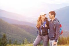 Unga lyckliga par med ryggsäcken i berg arkivbild