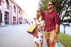 Unga lyckliga par med shoppingpåsar i staden Arkivbild