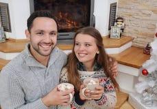 Unga lyckliga par med varm kakao dricker i väl till mods tröjasittin Arkivbild