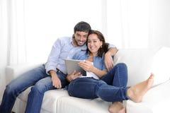 Unga lyckliga par på den hemmastadda tyckande om användande digitala minnestavladatoren för soffa Arkivbild