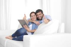 Unga lyckliga par på den hemmastadda tyckande om användande digitala minnestavladatoren för soffa Royaltyfria Bilder