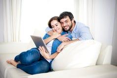 Unga lyckliga par på den hemmastadda tyckande om användande digitala minnestavladatoren för soffa Fotografering för Bildbyråer