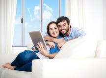 Unga lyckliga par på den hemmastadda tyckande om användande digitala minnestavlan för soffa Fotografering för Bildbyråer
