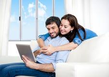Unga lyckliga par på den hemmastadda tyckande om användande digitala minnestavlan för soffa Royaltyfri Foto