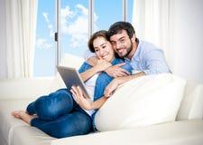 Unga lyckliga par på den hemmastadda tyckande om användande digitala minnestavlan för soffa Arkivbild