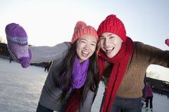 Unga lyckliga par på isisbanan Royaltyfri Foto