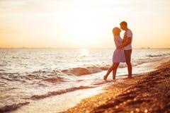 Unga lyckliga par på kusten royaltyfri bild