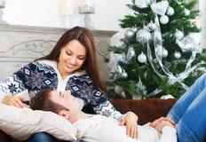 Unga lyckliga par på soffan vid det Cristmas trädet Arkivfoto