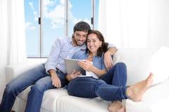Unga lyckliga par på den hemmastadda tyckande om användande digitala minnestavlan för soffa Royaltyfria Bilder