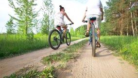 Unga lyckliga par som cyklar på banan i sommarfält arkivfilmer