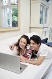 Unga lyckliga par som delar bärbara datorn på soffan Arkivbilder