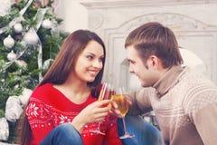 Unga lyckliga par som dricker champagne vid det Cristmas trädet Arkivfoto