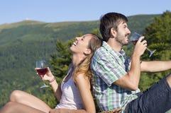Unga lyckliga par som dricker vin på en fotvandra tur på viewpoien Royaltyfri Fotografi