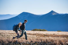 Unga lyckliga par som fotvandrar i de härliga bergen royaltyfria bilder