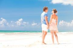 Unga lyckliga par som går på att le för strand. Royaltyfria Bilder
