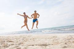 Unga lyckliga par som går på strandsolnedgång, semestrar arkivbilder