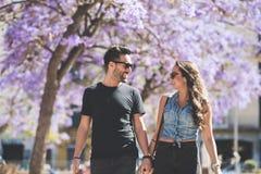 Unga lyckliga par som går rymma tillsammans händer Royaltyfri Foto