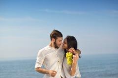 Unga lyckliga par som har datumet på kusten arkivbild