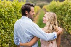 Unga lyckliga par som har en arm runt om de och att le arkivfoton