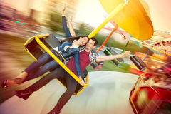 Unga lyckliga par som har gyckel på nöjesfältet Arkivbild