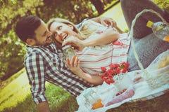 Unga lyckliga par som har picknicken i ängen Par som har f Royaltyfria Bilder