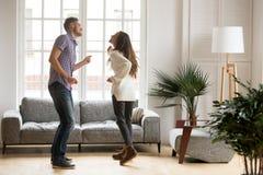 Unga lyckliga par som har roligt dansa tillsammans i vardagsrum royaltyfri fotografi
