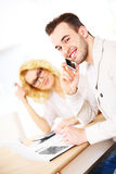 Unga lyckliga par som hemma arbetar på dokument Royaltyfri Foto