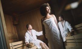 Unga lyckliga par som kopplar av inom en bastu p? lyx f?r brunnsortsemesterorthotell royaltyfri bild