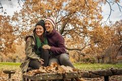 Unga lyckliga par som kramar att se bort, sitter i en bänk i PA Royaltyfri Fotografi