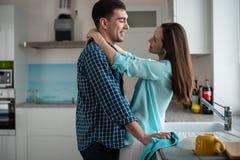 Unga lyckliga par som kramar och ser de i inre av ett nytt kök, lycka i ett nytt hem arkivfoton