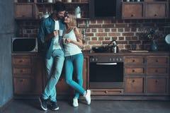 Unga lyckliga par som kramar och ser de i inre av ett nytt kök, lycka i ett nytt hem arkivfoto