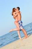 Unga lyckliga par som kysser på att omfamna för sandig strand Arkivbild