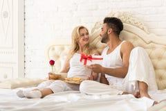 Unga lyckliga par som ligger i säng, den latinamerikanska mannen, ger kuvertet för kvinnaöverraskninggåva med bandet, årsdagberöm royaltyfri fotografi
