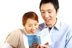 Unga lyckliga par som planerar en travel  Arkivfoton