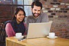Unga lyckliga par som ser en bärbar dator Arkivbilder