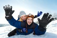 Unga lyckliga par som sledding i vinter Arkivbild