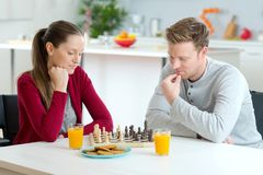 Unga lyckliga par som spelar den hemmastadda inre för schack Royaltyfria Foton