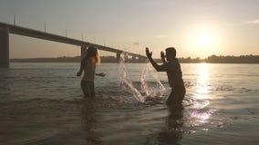 Unga lyckliga par som spelar i vattnet lager videofilmer