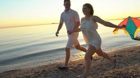 Unga lyckliga par som spelar med en drake på havet, sätter på land på solnedgången Man och kvinna som tillsammans tycker om tid p lager videofilmer