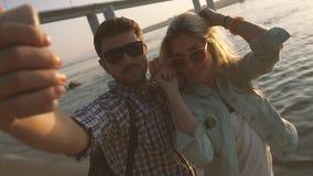 Unga lyckliga par som tar fotoet med mobiltelefonen utanför på stranden arkivfilmer