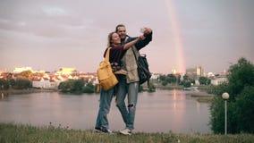 Unga lyckliga par som tar selfiefotona med regnbågen, nära floden på bakgrund Le man- och kvinnabrukssmartphonen arkivfilmer