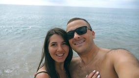 Unga lyckliga par som tar självståenden på havsstranden Le par som gör selfie på havkusten Gladlynt man och lager videofilmer